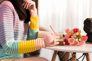 Close-up of Young woman in colorful fashionable sweater writing a diary and drawing in the book