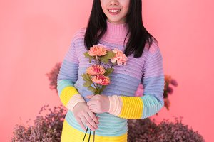 Close-up of Cheerful young woman holding bunch of flowers in colorful sweater isolated over pink background