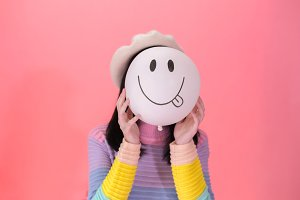 Young woman in colorful fashionable style holding a positive and lively emotion of balloon - joyful and cheerful expression
