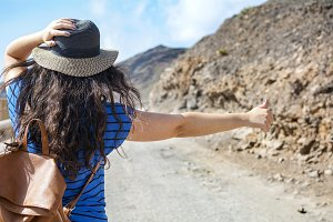Woman hitchhiking on her trip.