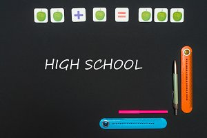 Black art table with stationery supplies with text high school on blackboard