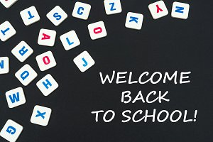 english colored square letters scattered on black background with text welcome back to school