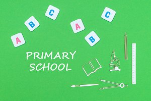 text primary school, from above wooden minitures school supplies and abc letters on green background