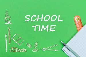 text school time, school supplies wooden miniatures, notebook with ruler, pen on green backboard