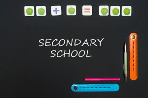Black art table with stationery supplies with text secondary school on blackboard