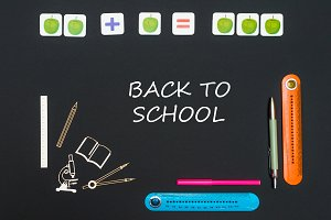 Above stationery supplies and text back to school on blackboard