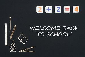 School supplies placed on black background with text welcome back to school