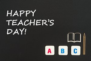 abc letters and chipboard miniature on blackboard with text happy teacher's day