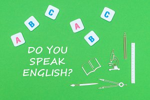 text do you speak english, from above wooden minitures school supplies and abc letters on green background