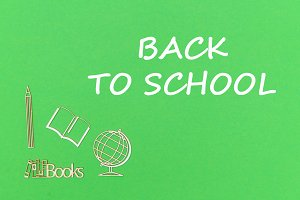 text back to school, school supplies wooden miniatures on green background