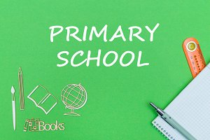 text primary school, school supplies wooden miniatures, notebook on green background