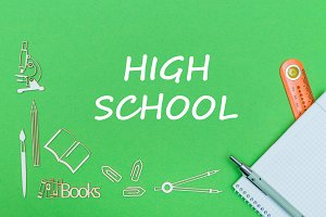text high school, school supplies wooden miniatures, notebook with ruler, pen on green backboard