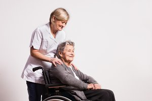 Studio portrait of a senior woman in wheelchair and a nurse.