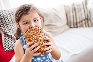 A small girl at home eating a loaf of bread.