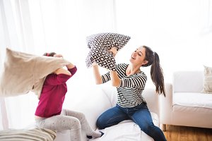 Young mother with a small girl at home having pillow fight.