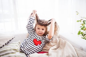 A small happy girl in striped T-shirt at home having fun.