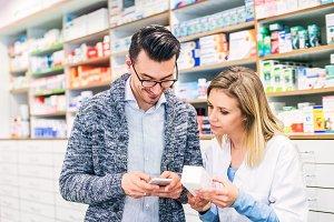 Female pharmacist serving a male customer.