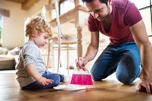 Handsome father and toddler boy with brush and dustpan.