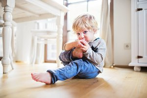 A toddler boy sitting on the floor at home.