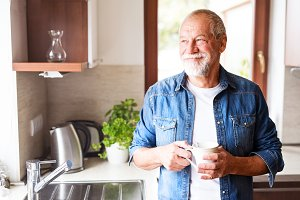 Happy senior man holding a cup of coffee in the kitchen.