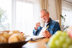 Senior man eating breakfast and doing crosswords at home.