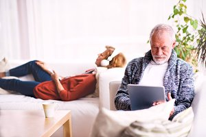 Senior couple with tablet and headphones relaxing at home.