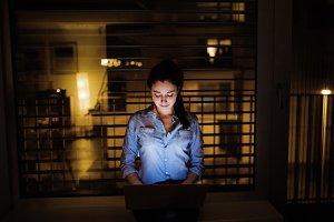 A woman working on a laptop at home or in the office at night.