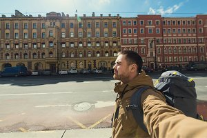 Young hipster man traveling backpacker outdoor in Saint-Petersburg street. Travel, hiking concept.