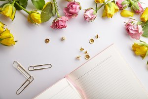 Overhead image of feminine workplace with flowers and pink notebook