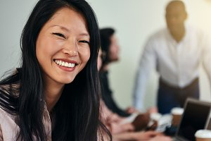 Smiling young Asian businesswoman at work in a modern office
