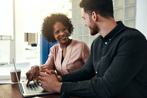 Smiling office colleagues working online together on a laptop