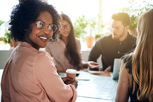 Smiling African businesswoman sitting with diverse coworkers in a boardroom