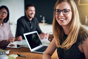 Smiling young businesswoman sitting with colleagues in a boardroom