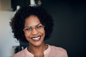 African businesswoman standing in a modern office smiling