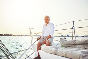 Mature man sitting on his boat enjoying a day sailing