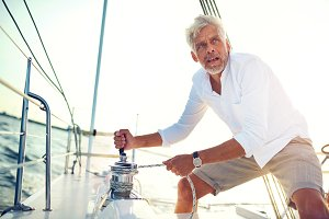 Mature man winching sail ropes on his boat