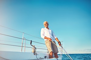 Smiling mature man enjoying a day sailing on the ocean