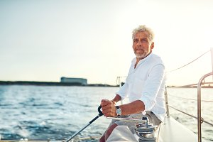Mature man sitting alone on the deck of his sailboat