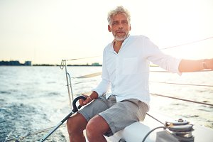 Mature man sitting on the deck of a sailboat
