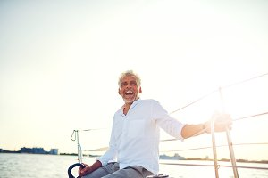 Laughing mature man enjoying a day sailing his yacht