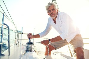 Mature man standing on his boat using a winch
