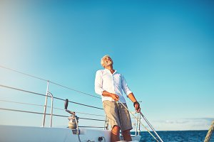Mature man looking skyward while out sailing on his boat