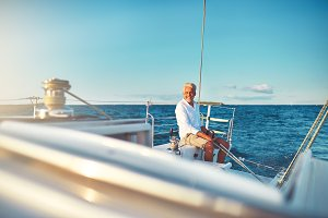 Smiling mature man sailing his yacht at sea