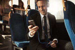 Smiling businessman listening to music on his morning commute