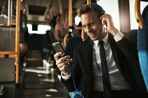 Smiling businessman reading texts and wearing headphones on a bus