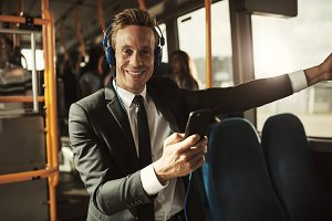 Smiling young businessman standing on a bus listening to music