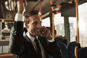 Smiling businessman standing on a bus talking on his cellphone
