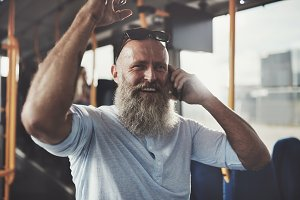 Smiling mature man riding a bus talking on his cellphone