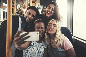 Smiling diverse friends taking selfies together on a bus