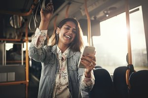 Young woman laughing while listening to music on a bus